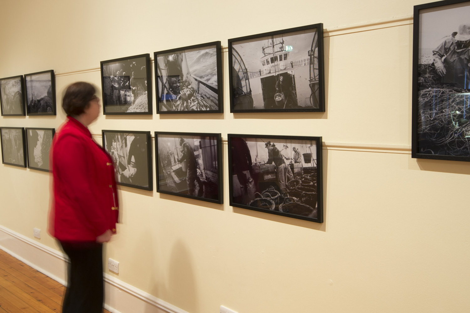 lady looking at a series of framed prints on a wall.