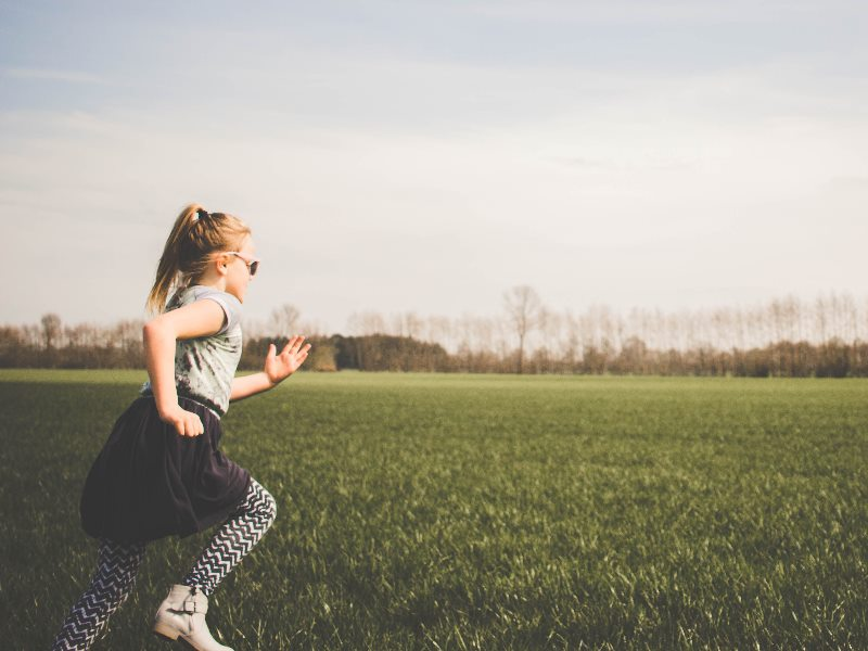 A girl running on a grass playing field