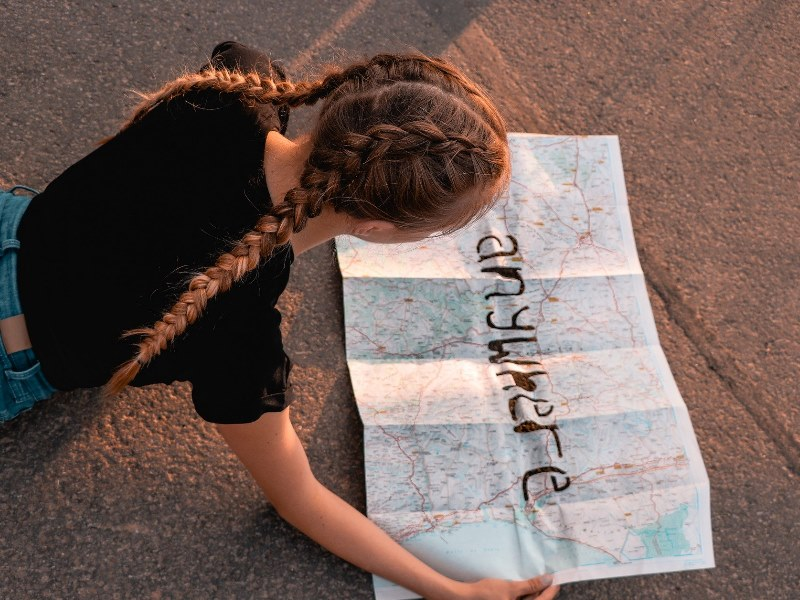girl lying on the ground looking at a map with the words Anywhere written on it