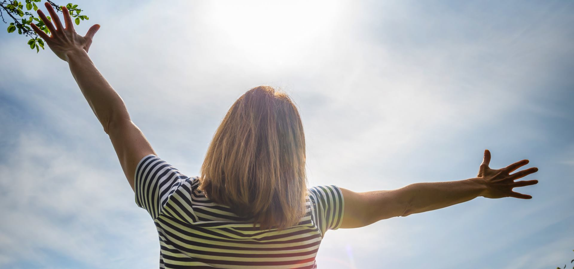 A woman outside reaching for the sky breathing in fresh air
